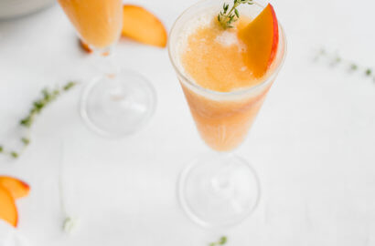 Peach Wine Slush with thyme as garnish and a fresh peach slice