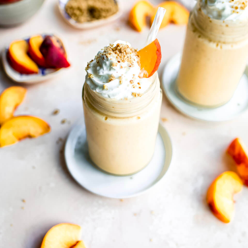 Peaches and Cream Smoothies with whipped cream and pecan crisp topping