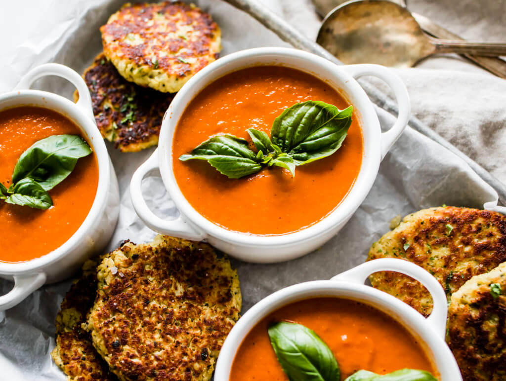 Whole30 Roasted Tomato basil soup garnished with fresh basil and a cauliflower fritter