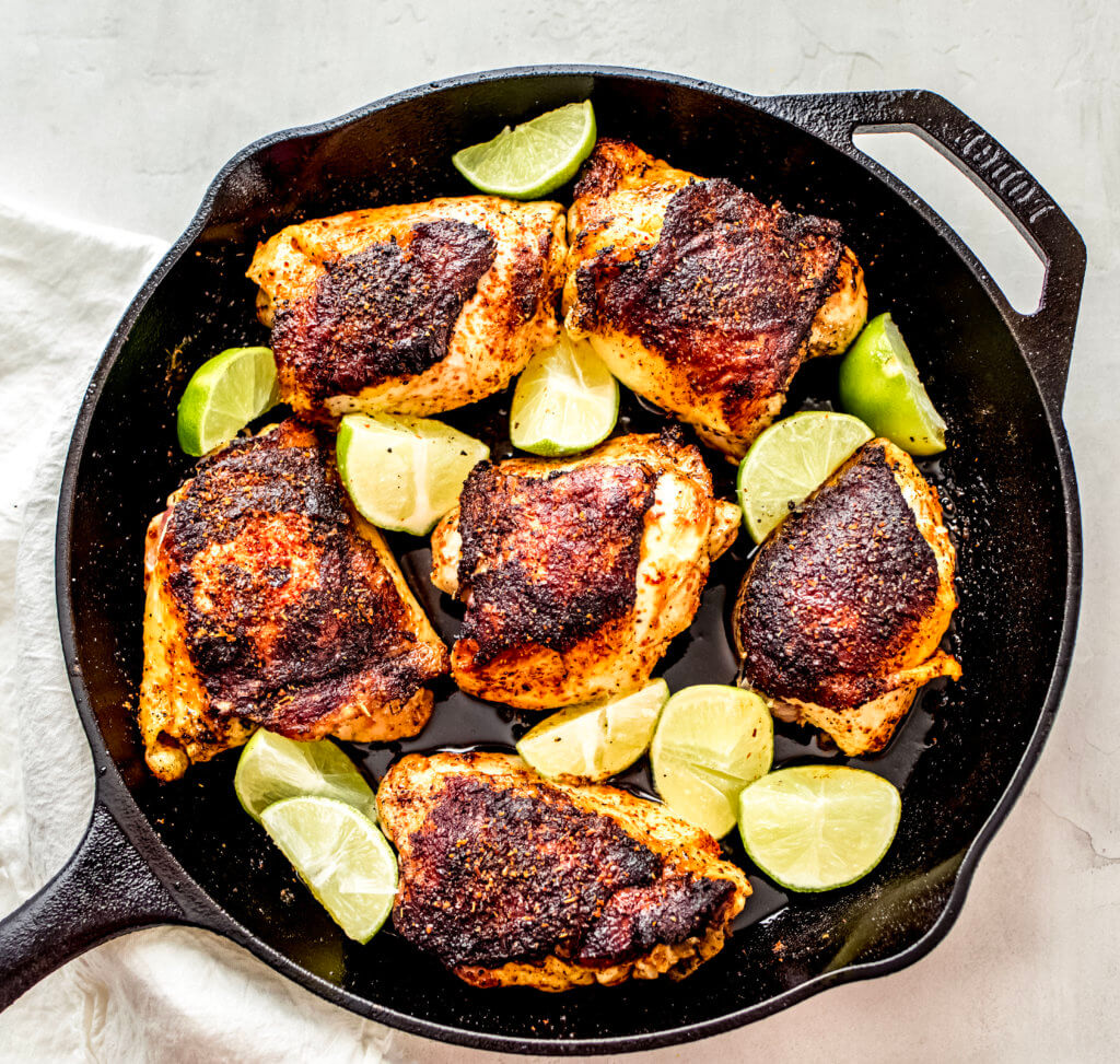 Overhead view of the chicken thighs with limes in a cast iron skillet