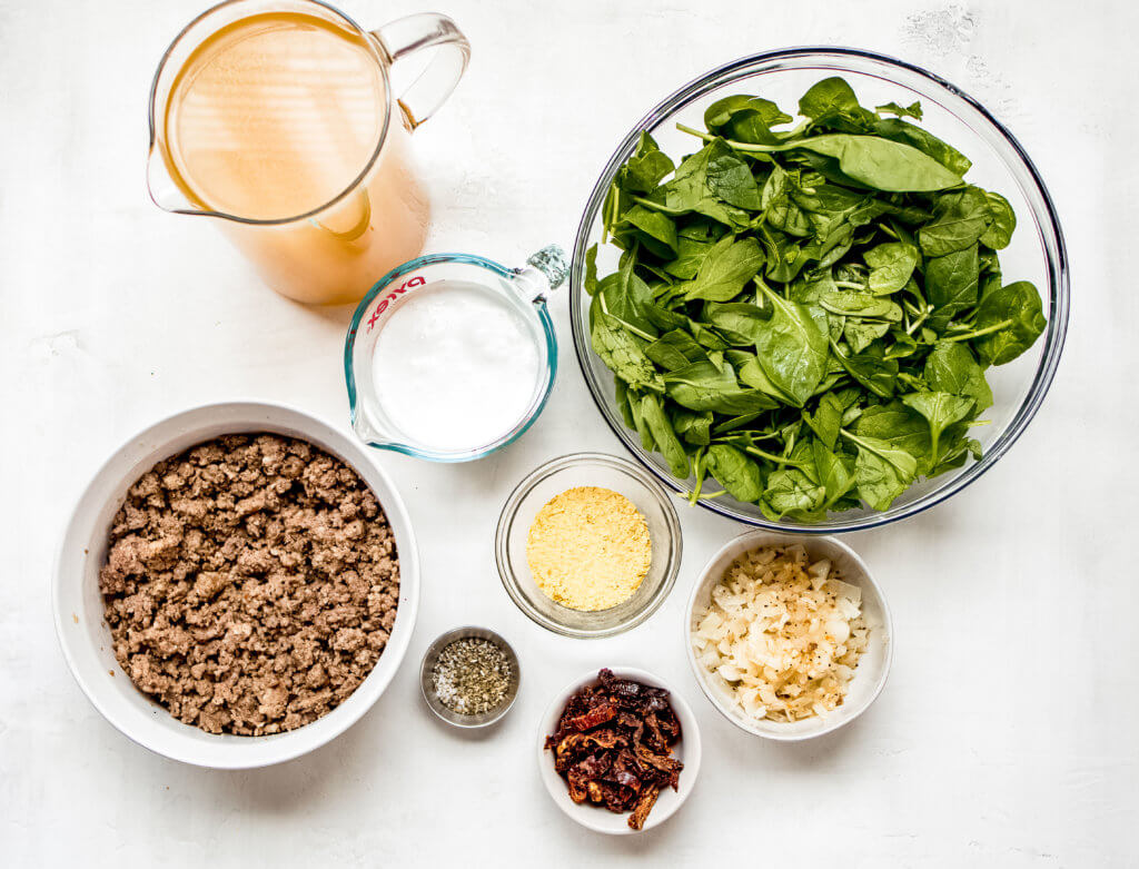 Ingredients for the soup. Ground sausage, chicken, broth, coconut milk, onions, garlic, sundried tomatoes, spinach and nutrtional yeast