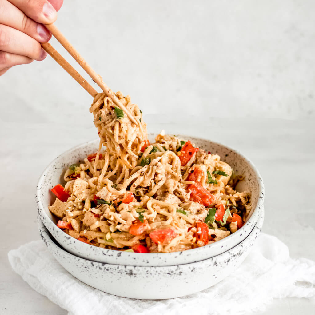 A side view of of the chicken Thai  noodles holding up with chop sticks