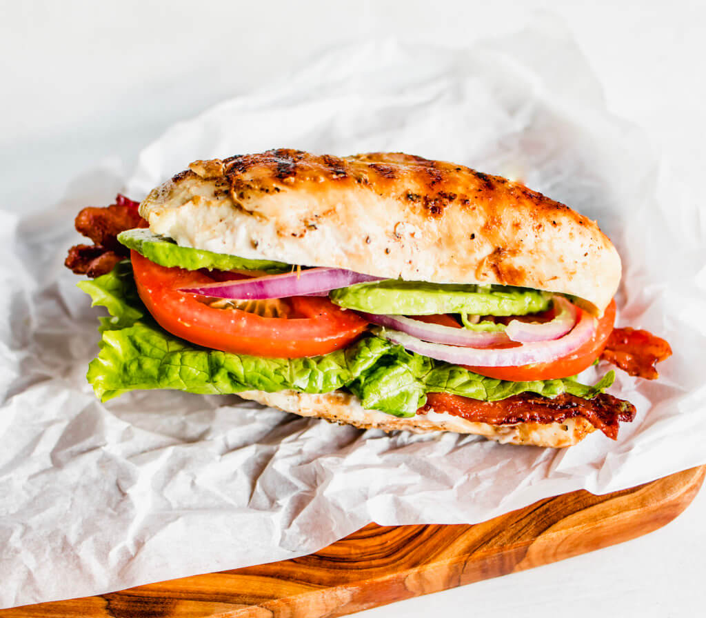 A front view of chicken breast stuffed with bacon, mayo, lettuce, onions tomato and avocado