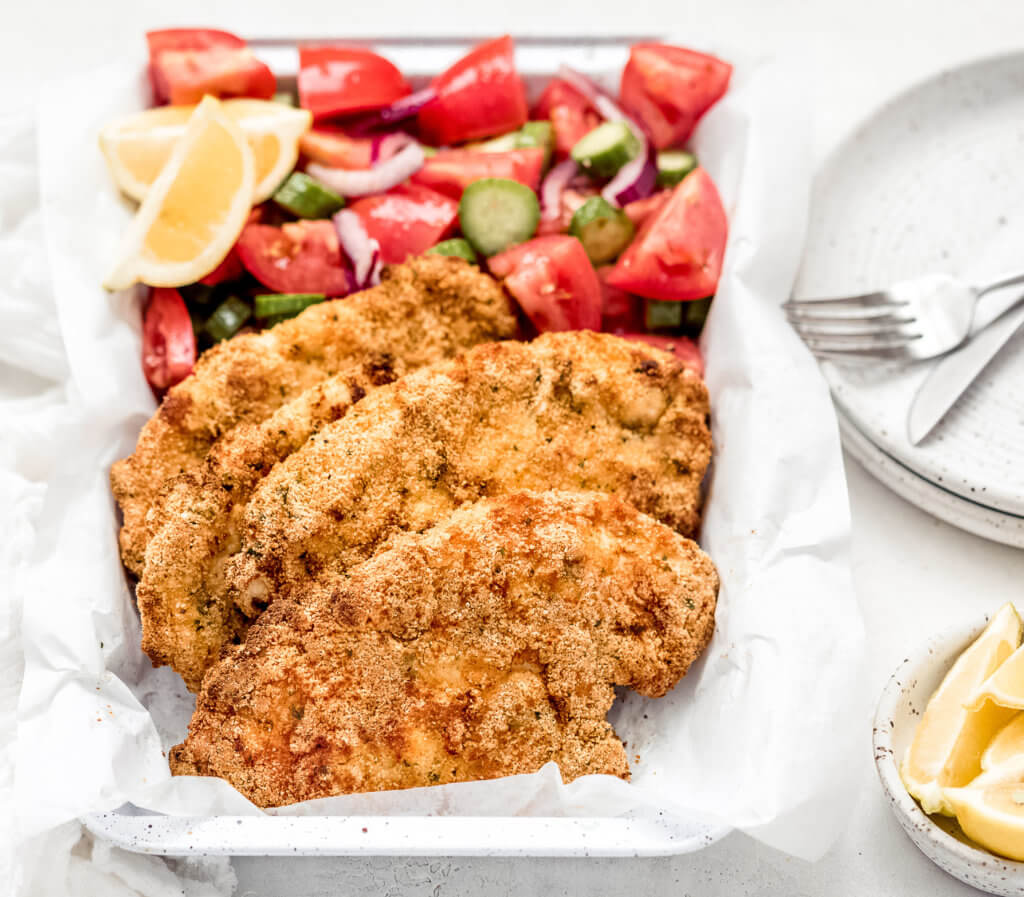 A side shot of the chicken schnitzel and tomato and cucumber salad