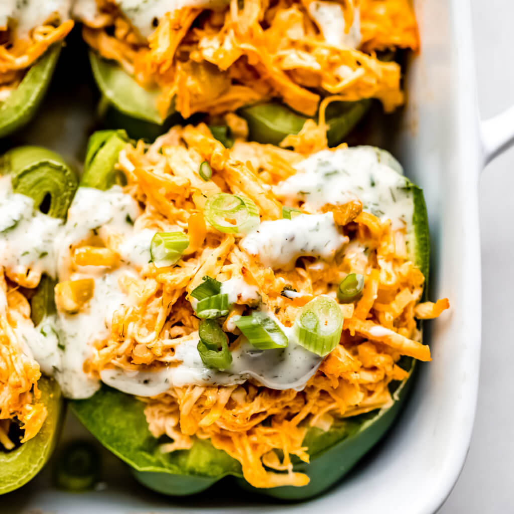 A close up photo of the stuffed peppers with ranch and green onions