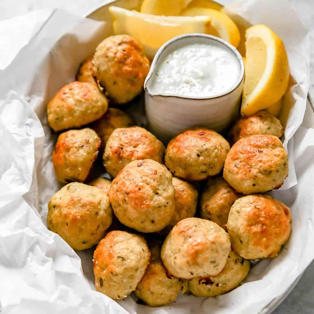 Meatballs with lemon slices and tzatziki sauce.