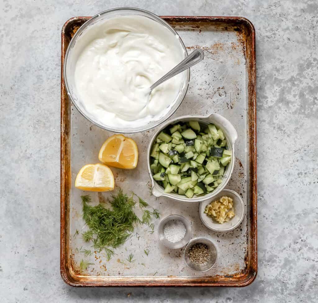 a sheet pan with Greek yogurt, diced cucumber, dill, lemon, garlic, salt and pepper