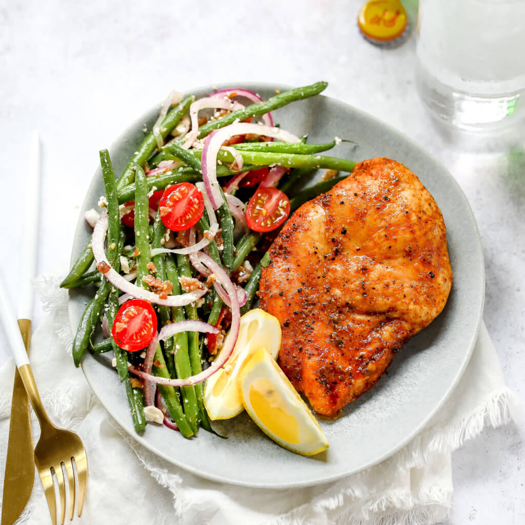 A photo of a plate with a chicken breast, lemon slices and green bean salad