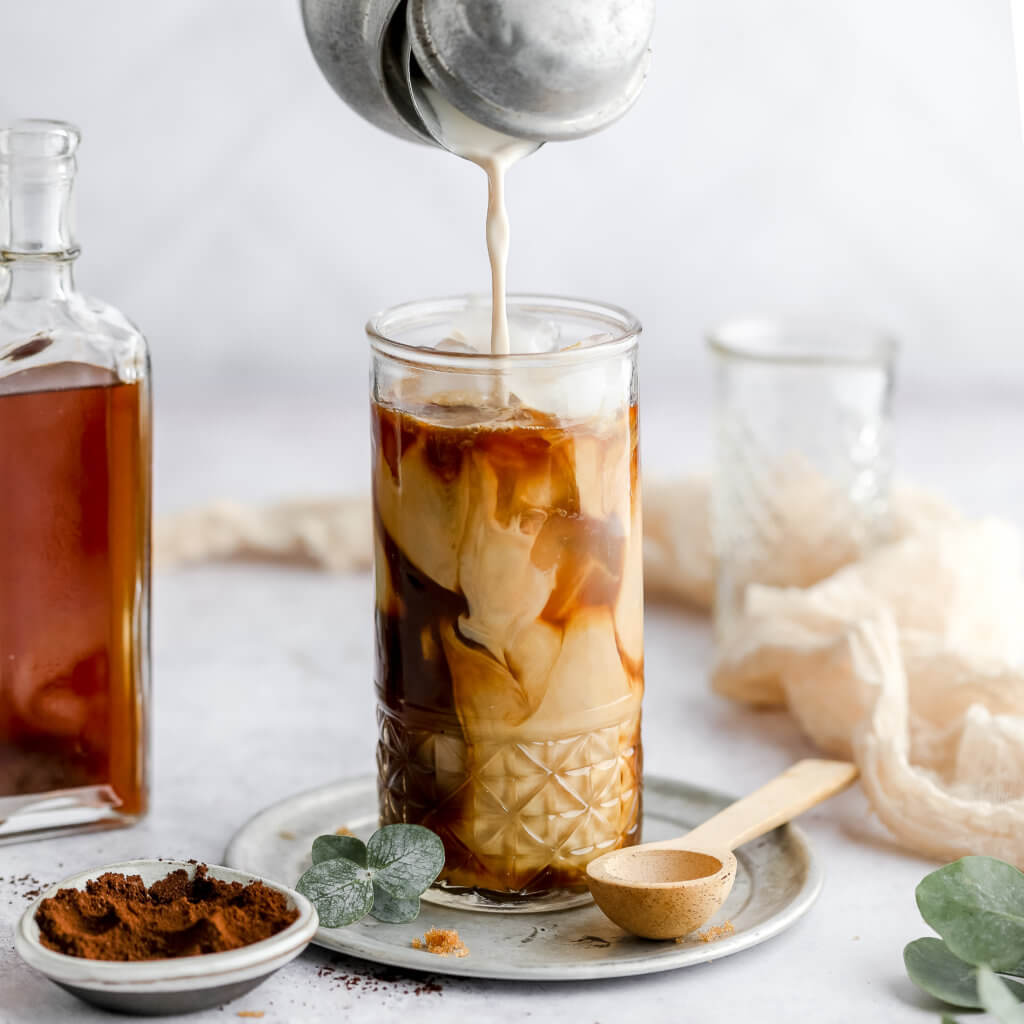 keto brown sugar latte in a tall glass with a silver carafe pouring almond milk into the glass, a glass bottle filled with brown sugar syrup next to the glass, and a pinch bowl filled with cinnamon with a white background.
