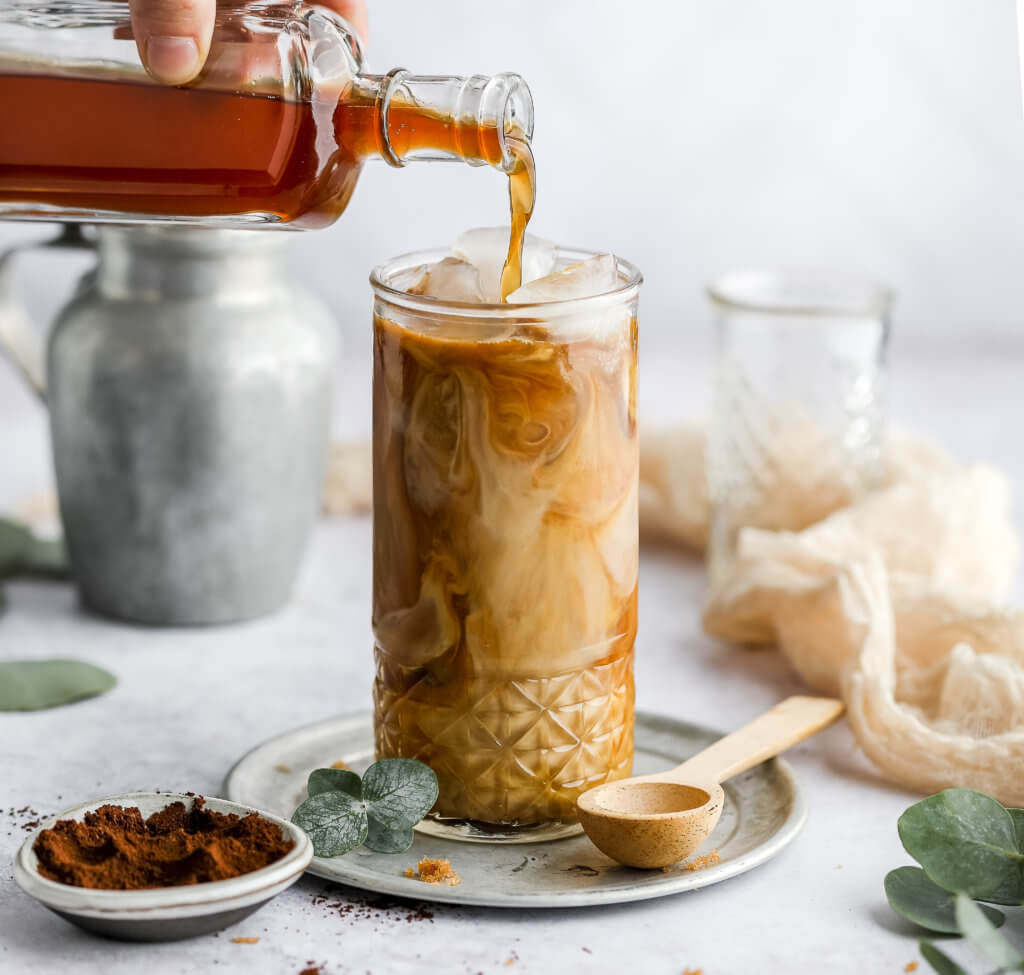 keto brown sugar latte in a tall glass with a glass bottle pouring brown sugar syrup into the glass, a silver carafe next to the glass, and a pinch bowl filled with cinnamon with a white background.
