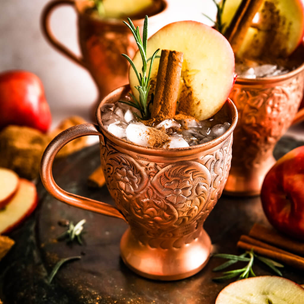 A front shot of the antique copper mug with ice, cinnamon and a apple slice