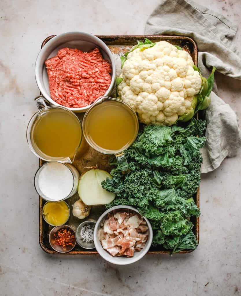 cauliflower head, ground sausage, chicken broth, kale, onion, unsweetened coconut milk, garlic, salt, pepper, red pepper flakes, ghee all on a baking sheet.